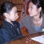 A big partner paints her little partner's face. (Photo by Jenny Broman '10)