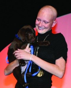 Katrina Siebels receives a puppy from anonymous donors during the 2009 live auction to celebrate her successful battle with cancer.