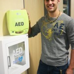 Joe Thayer '15 next to the AED located in Beck Academic Hall (Photo by Matt Thomas '00).